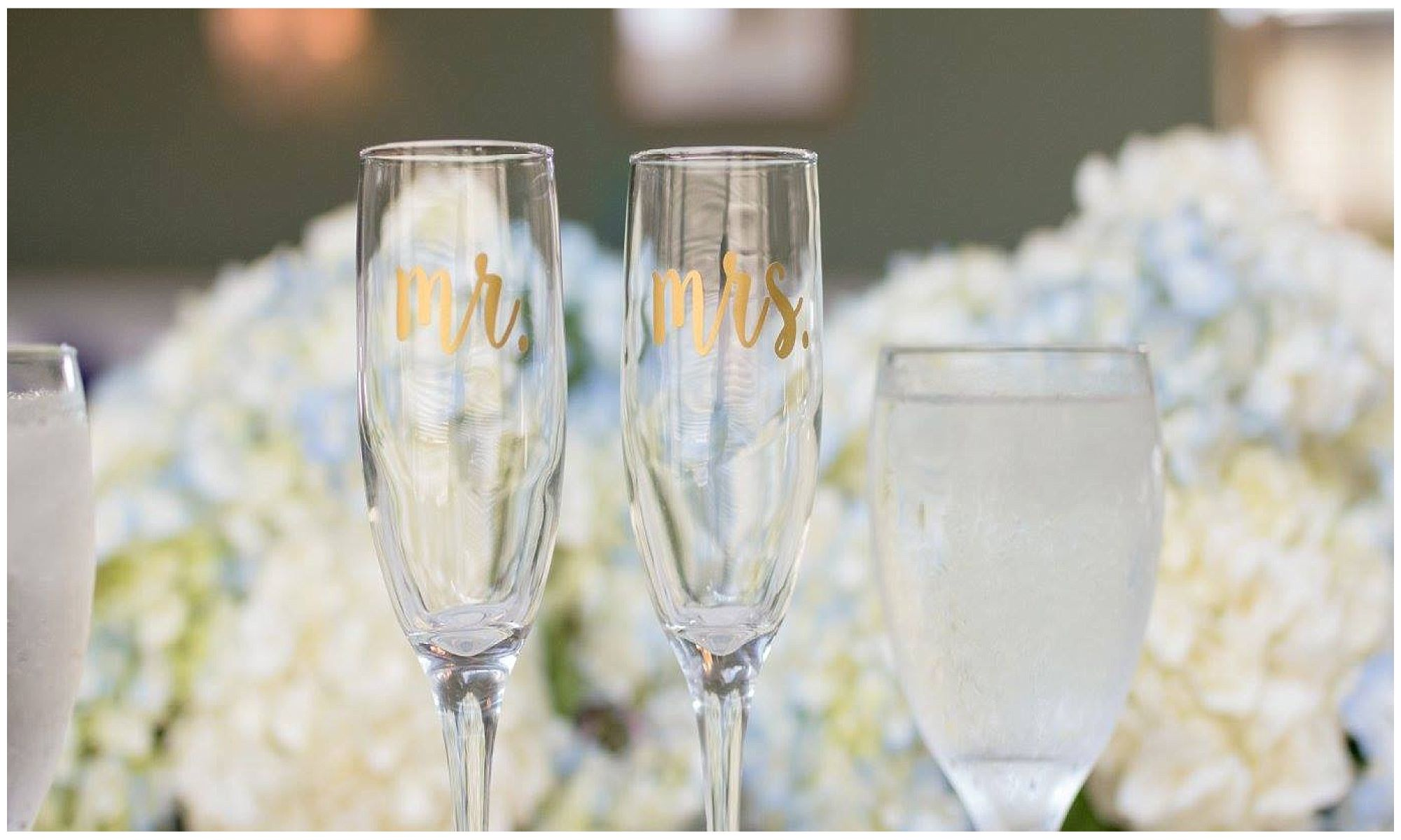 clear Mr and Mrs Champagne glasses against a flower backdrop