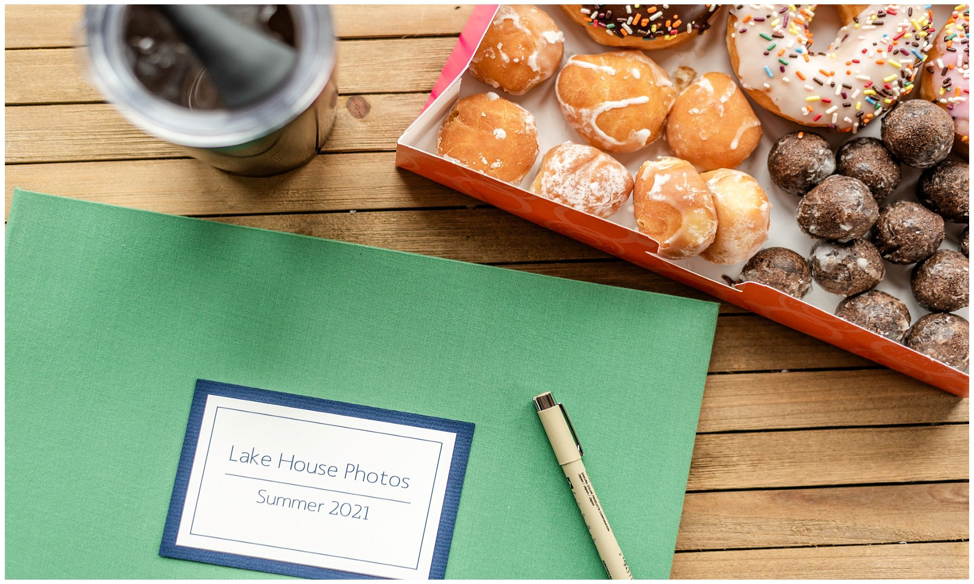 Vacation Home Guest Book green cover next to donuts and coffee on a wooden background