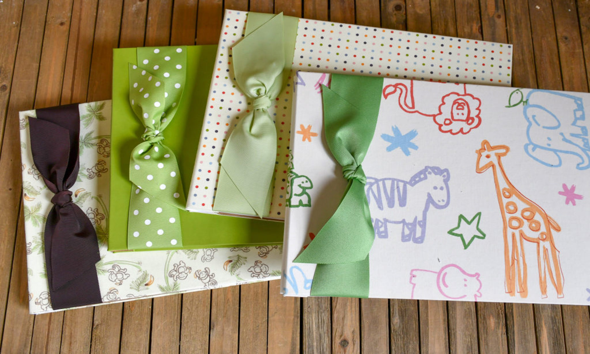 Baby Memory Books with ribbons on wooden background