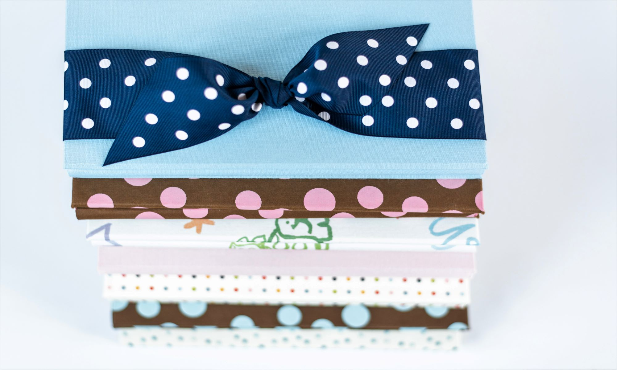 Stack of Baby Memory Books with blue cloth cover and blue dot bow on top